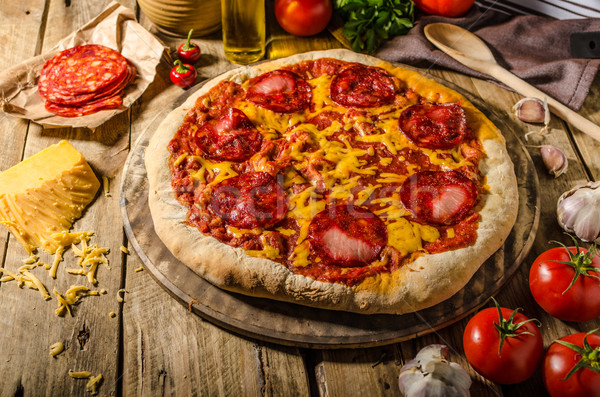 Rustic salami pizza with cheddar cheese and chorizo Stock photo © Peteer
