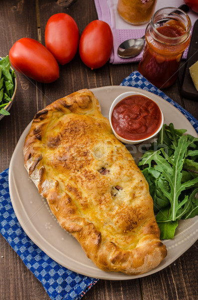 Calzone pizza stuffed with cheese and prosciutto Stock photo © Peteer