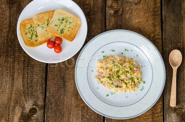 Scrambled eggs with chive and bacon, toast with herbs Stock photo © Peteer