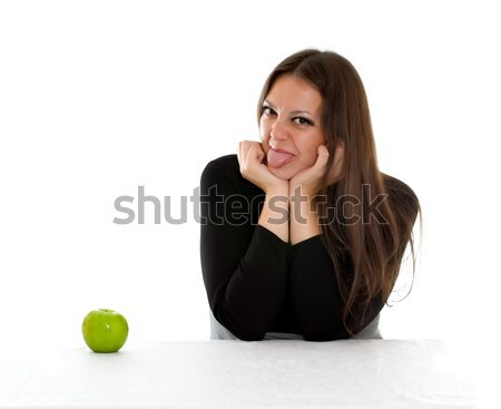 girl with grimace on her face and green apple Stock photo © PetrMalyshev