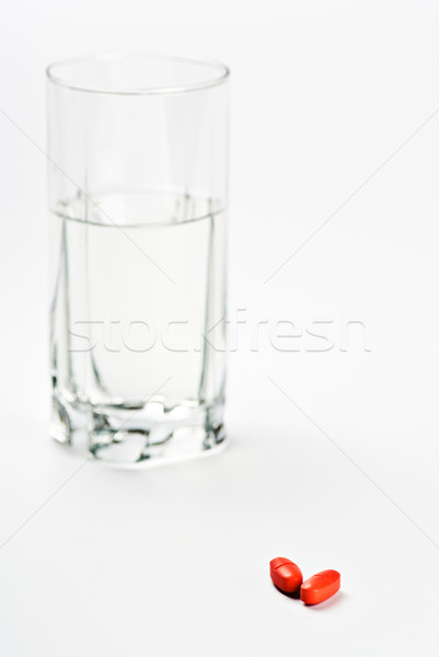 Stock photo: two red pills and glass of water