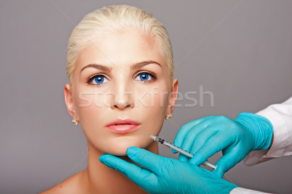 Cosmetic plastic surgeon injecting aesthetics face Stock photo © phakimata