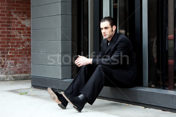 Homme d'affaires séance élégant costume noir rue Photo stock © phakimata