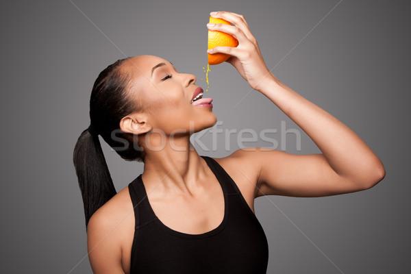 Happy healthy black asian woman squeezing orange juice fruit Stock photo © phakimata