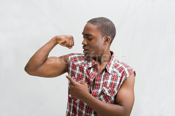 Jeunes élégant Guy sombre pointant biceps Photo stock © phakimata