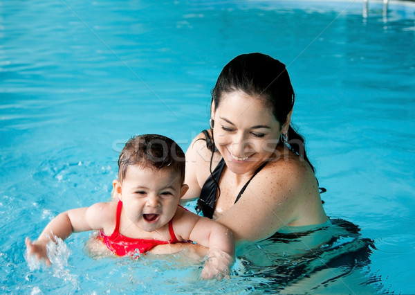 Mother teaching baby swimming Stock photo © phakimata