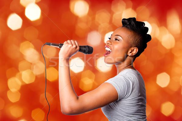 Singing kareoke woman with microphone Stock photo © phakimata