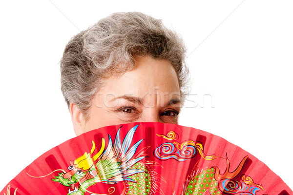 Senior woman with red dragon fan Stock photo © phakimata