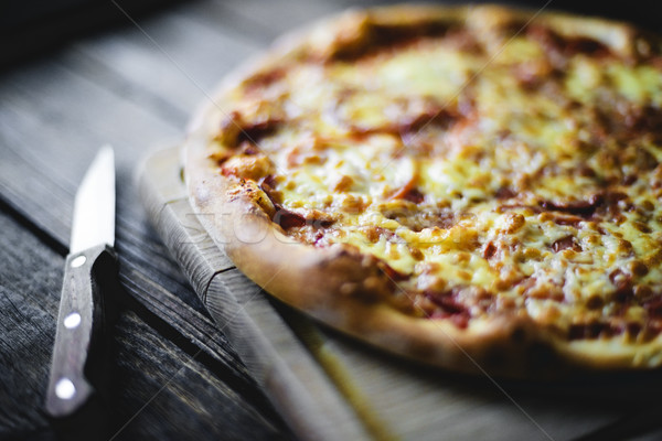 Pizza on the cutting board and knife beside Stock photo © Phantom1311