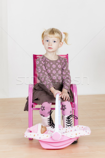 Little girl jogar boneca menina criança cadeira Foto stock © phbcz