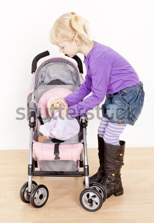 little girl playing with a doll and a stroller Stock photo © phbcz