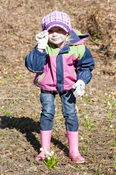 Stock photo: little girl wearing rubber boots with snowflakes in spring natur