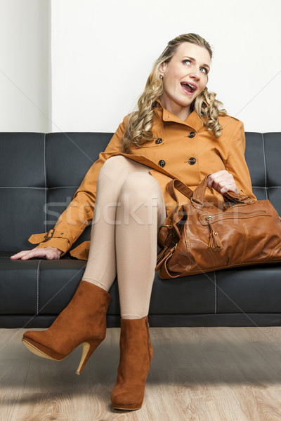 woman wearing brown coat with a handbag sitting on sofa Stock photo © phbcz