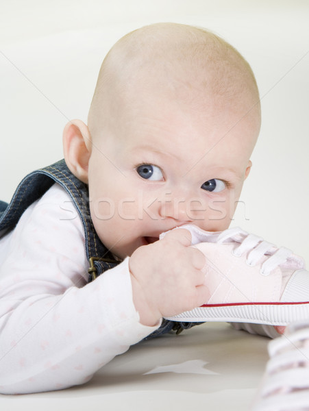 Stock photo: portrait of lying down baby girl holding a shoe