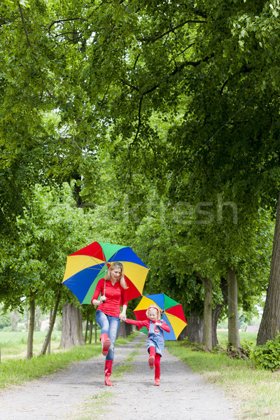 mother and her daughter with umbrellas in spring alley Stock photo © phbcz