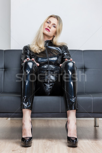 woman wearing black extravagant clothes and pumps sitting on sof Stock photo © phbcz