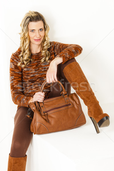 sitting woman wearing brown clothes and boots with a handbag Stock photo © phbcz
