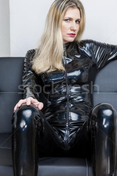 portrait of woman wearing black extravagant sitting on sofa Stock photo © phbcz