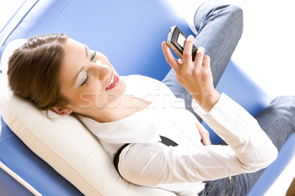 woman with mobile phone lying on sofa Stock photo © phbcz