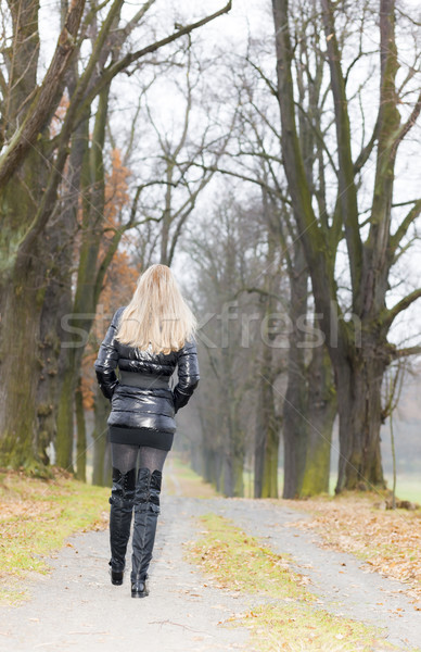 woman wearing black clothes and boots in autumnal alley Stock photo © phbcz