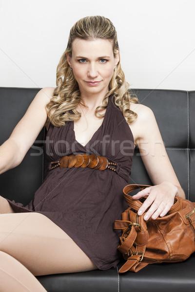 portrait of woman with a handbag sitting on sofa Stock photo © phbcz