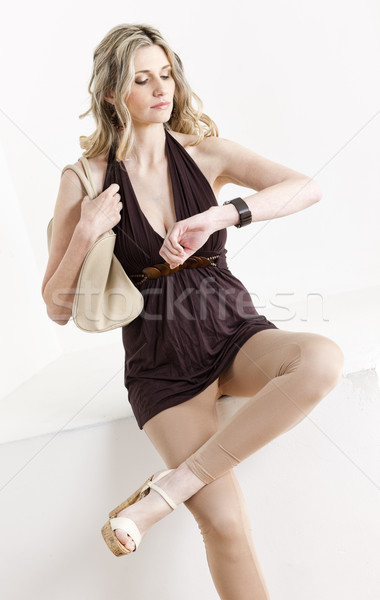 sitting woman looking at wristwatch Stock photo © phbcz