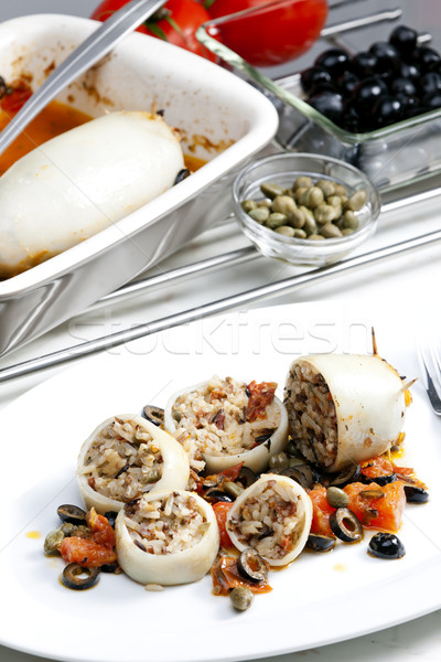 baked sepia with tomatoes and black olives filled with pearl bar Stock photo © phbcz