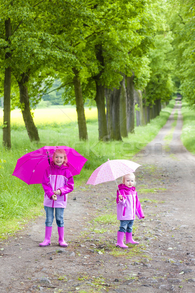 little girls wearing rubber boots with umbrellas in spring alley Stock photo © phbcz