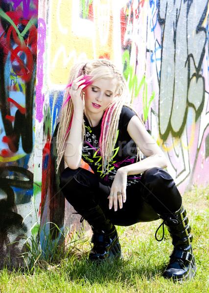 young woman sitting at graffitti wall Stock photo © phbcz