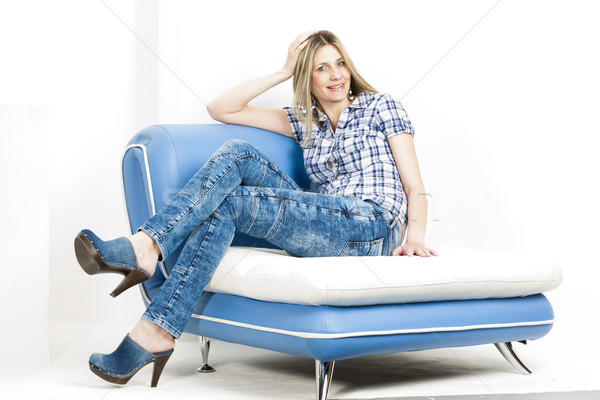 woman sitting on sofa wearing jeans and denim clogs Stock photo © phbcz