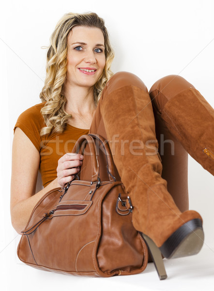 portrait of sitting woman wearing brown clothes and boots with a Stock photo © phbcz