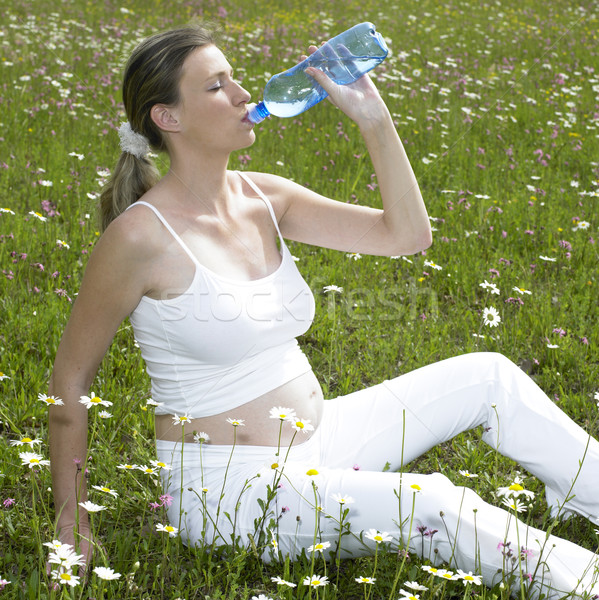 pregnat woman on meadow with bottle of water Stock photo © phbcz