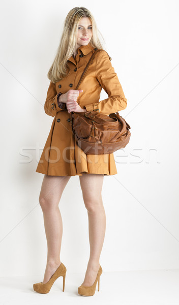 standing woman wearing brown coat and pumps with a handbag Stock photo © phbcz