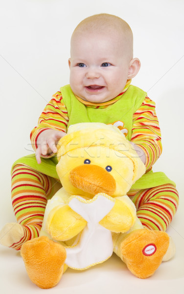 sitting baby girl with a duck toy Stock photo © phbcz