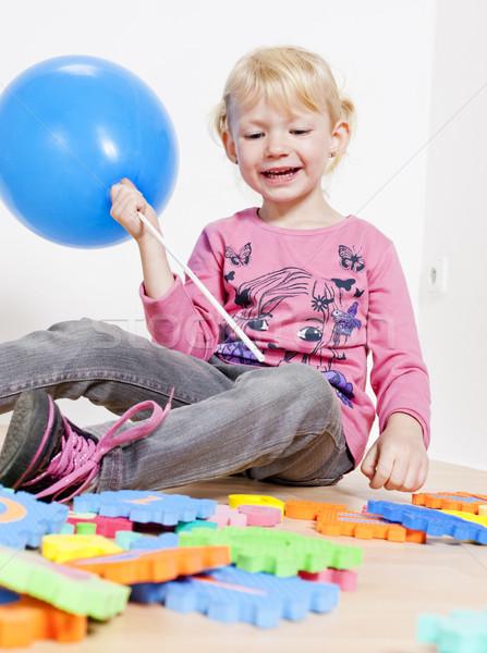 Stock photo: playing little girl holding balloon