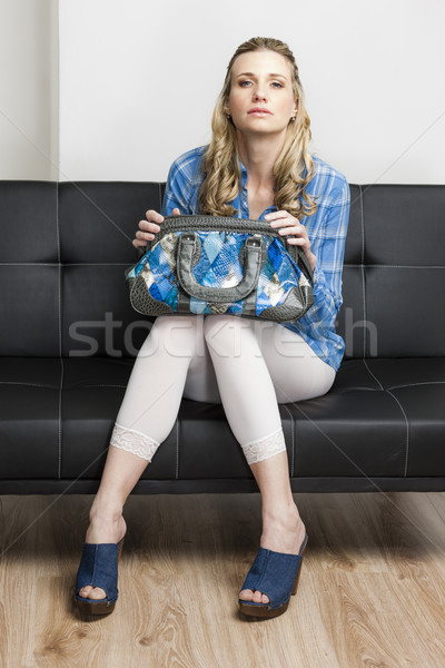 woman wearing denim clogs with a handbag sitting on sofa Stock photo © phbcz