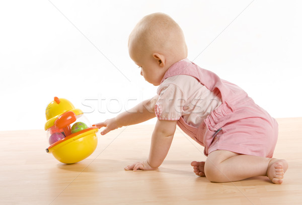 baby girl crawling towards a toy on the floor Stock photo © phbcz