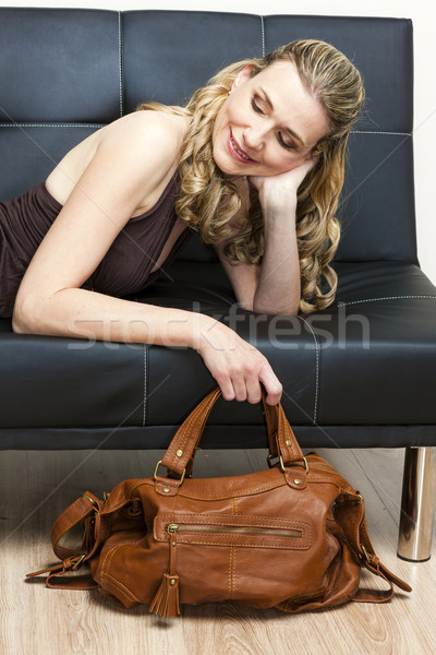 portrait of woman with a handbag lying on sofa Stock photo © phbcz