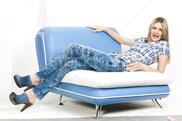 woman on sofa wearing jeans and denim clogs Stock photo © phbcz