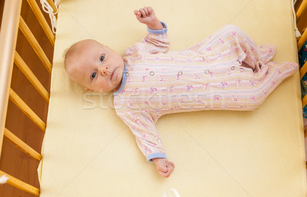 lying two month old baby girl in cot Stock photo © phbcz
