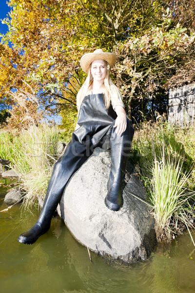 Rybak kobieta posiedzenia kamień połowów hat Zdjęcia stock © phbcz