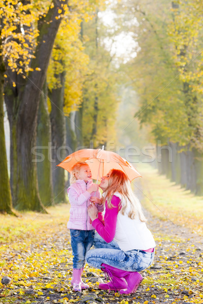 mother and her daughter with umbrella in autumnal alley Stock photo © phbcz