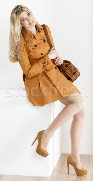 sitting woman wearing brown coat and pumps with a handbag Stock photo © phbcz