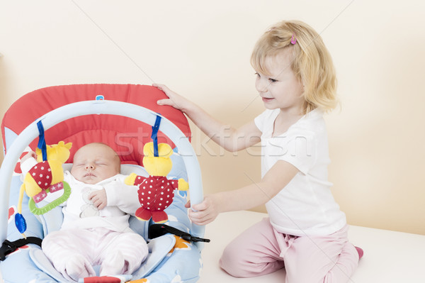 portrait of a little girl with her baby sister sleeping in a cha Stock photo © phbcz