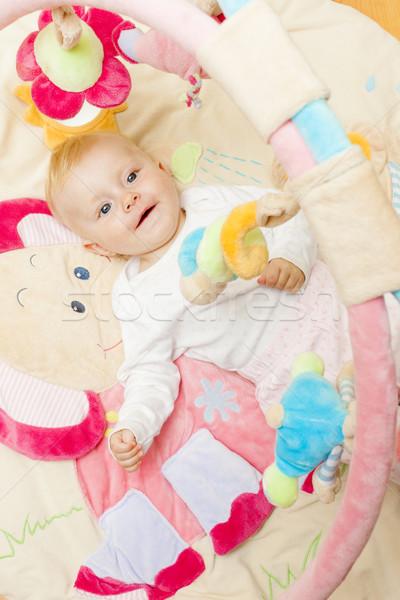 portrait of baby girl lying on playing mat Stock photo © phbcz