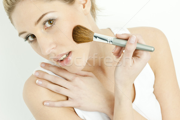 portrait of young woman putting on face powder Stock photo © phbcz
