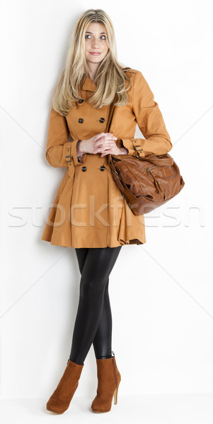 standing woman wearing coat and fashionable brown shoes with a h Stock photo © phbcz