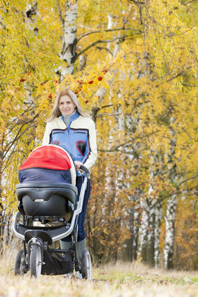 Stock photo: woman with a pram on walk in autumnal nature