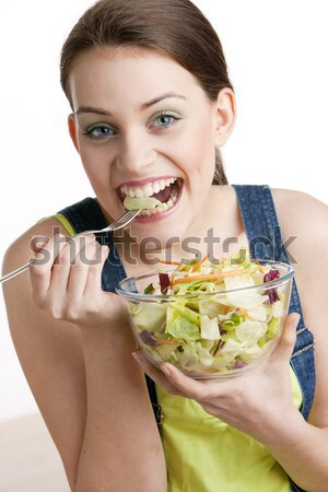 Stock photo: portrait of lying down woman eating salad