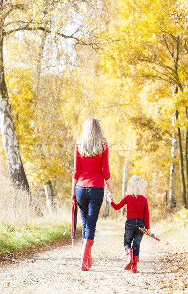 mother with her daughter with umbrellas in autumnal alley Stock photo © phbcz